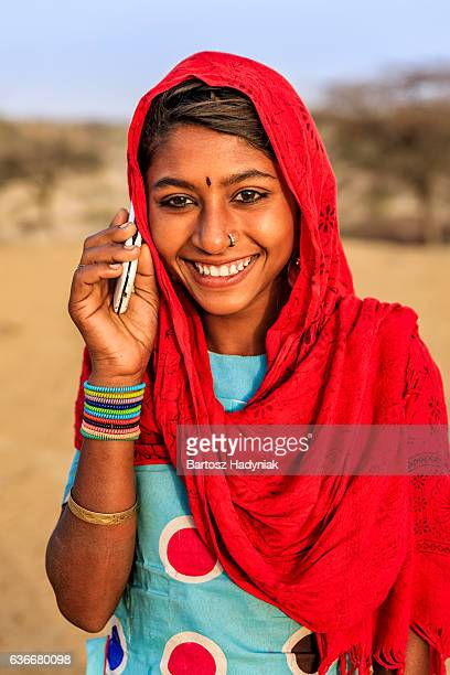 Happy Indian girl using mobile phone in desert village, India