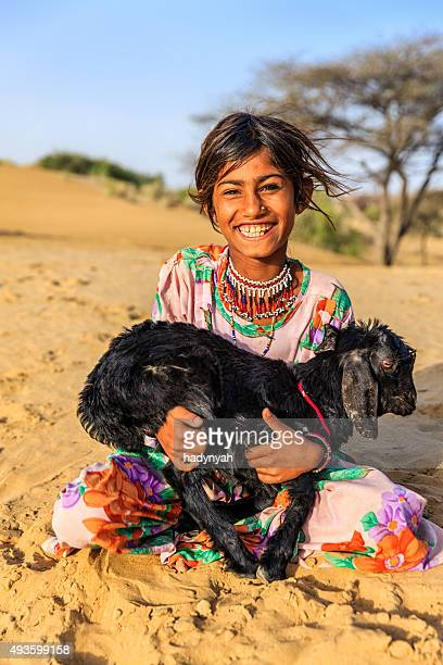 Happy Indian little girl holding a goat, desert village, India