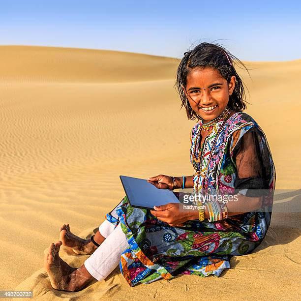 Happy Indian little girl using digital tablet, desert village, India