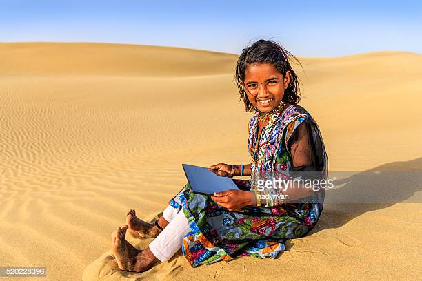Happy Indian little girl using digital tablet, desert village, India