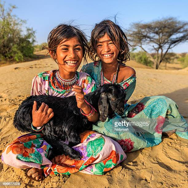 Happy Indian little girls holding a goat, desert village, India