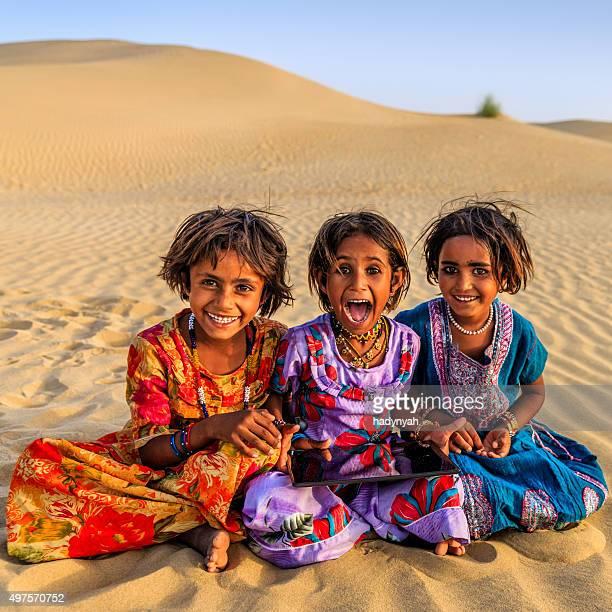 Heureux Indian petites filles à l'aide de tablette numérique, desert village, India