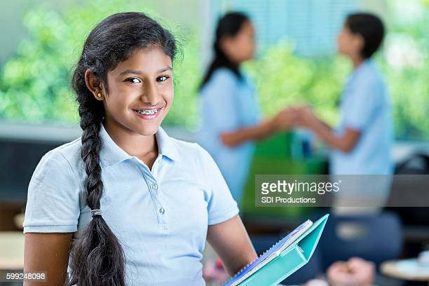 Happy Indian middle school student smiles before class