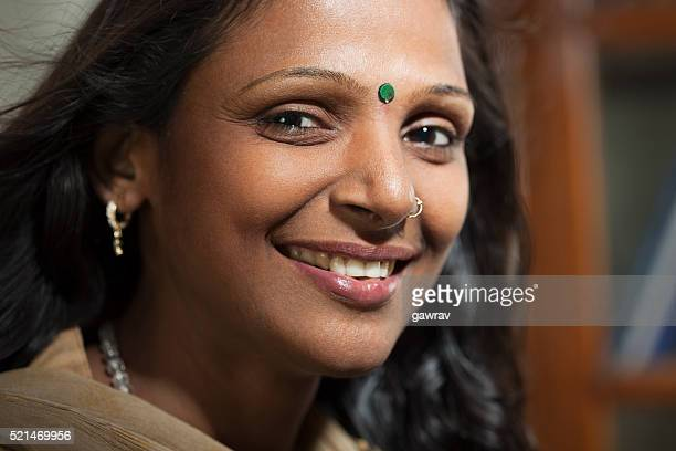 Happy Indian woman looking at camera with toothy smile.
