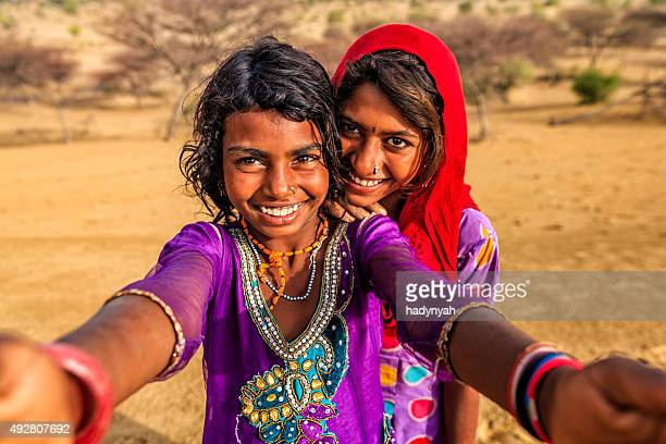 Happy Indian young girls taking selfie, desert village, India
