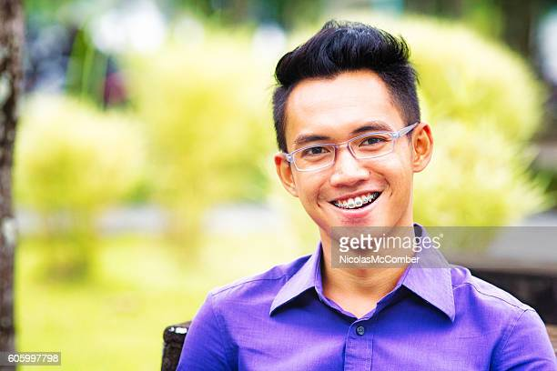 Happy Indonesian male student portrait with braces and glasses