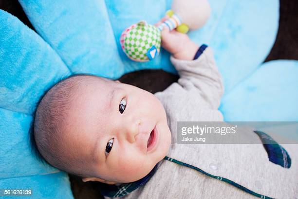 Happy infant boy holding toy and lying on mat
