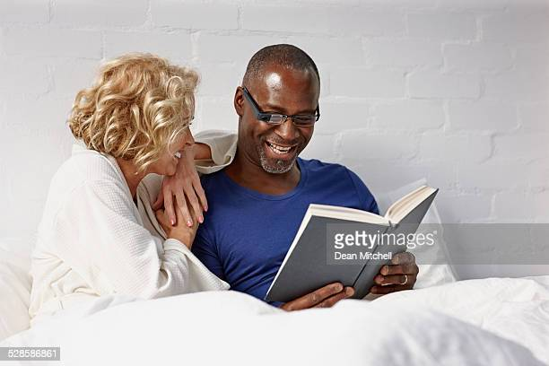 Happy interracial couple reading book on bed