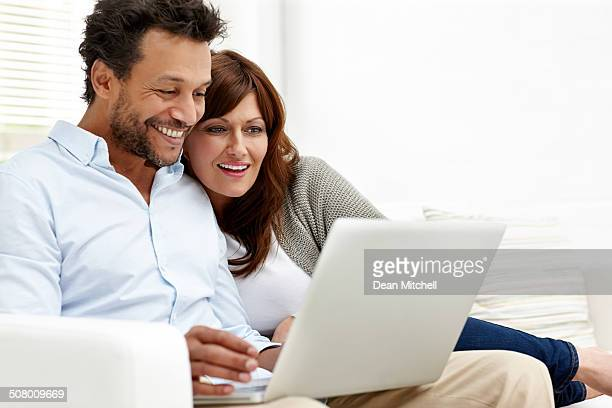 Happy interracial couple using laptop