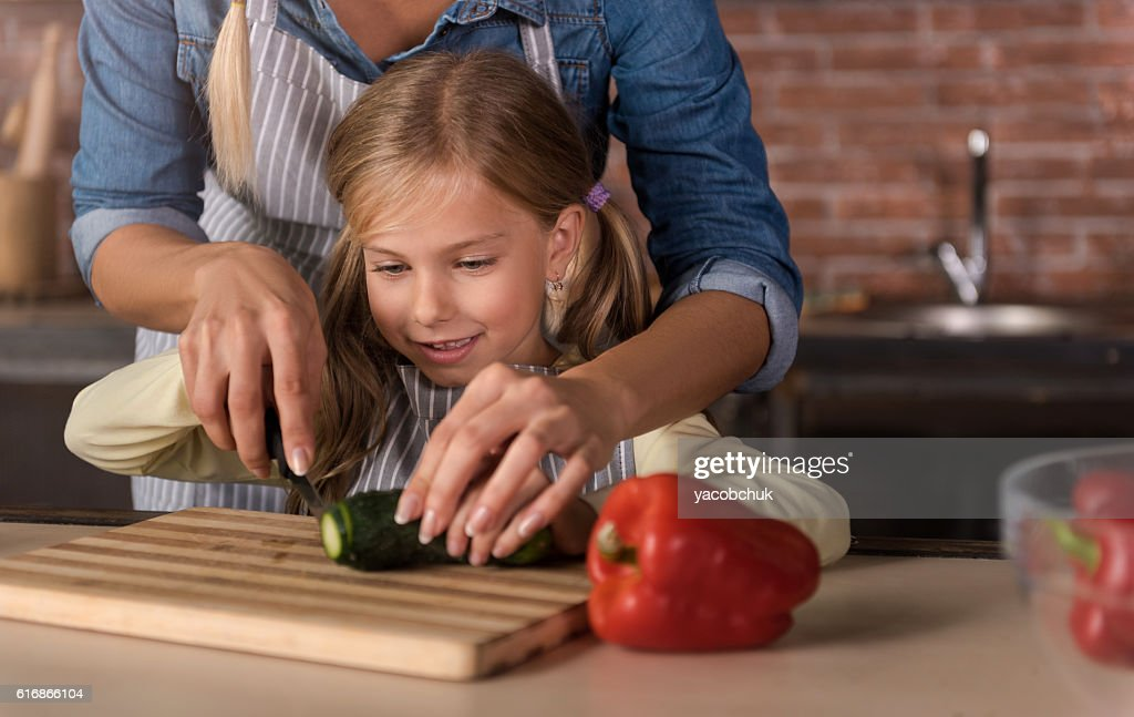 Happy involved girl cutting a cucumber with her mother : Stock Photo