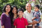 This happy Filipino family, mother, daughter, father and sons, pose outside in a tropical, park like setting in sunny Hawaii. Families can be together forever.