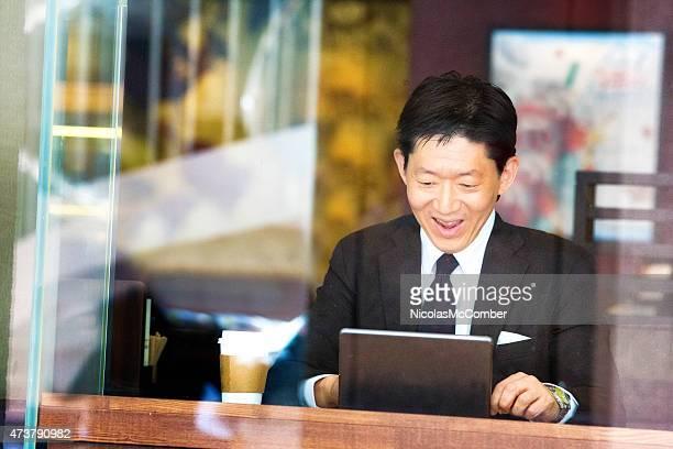 ハッピーな日本の実業家のタブレットの良いニュースを読むのカフェ