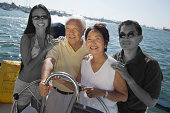 Happy Japanese family sailing together on yacht