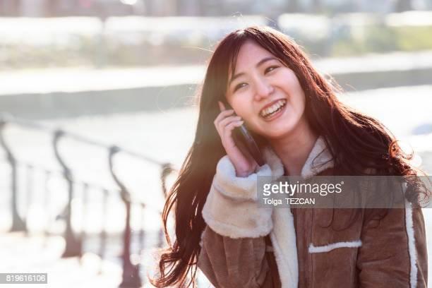 Happy japanese woman talking smartphone, Copenhagen