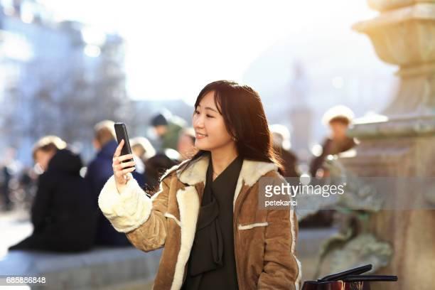 Happy japanese woman tourist taking selfie  in Nyhavn, Copenhagen