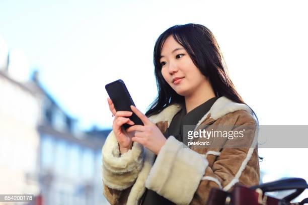 Happy japanese woman using smartphone, Copenhagen