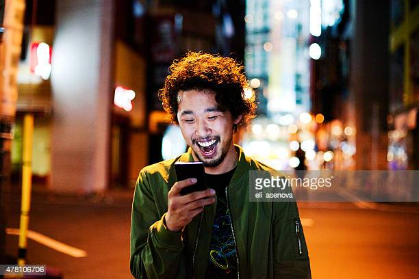 Happy japanische junger Mann mit Smartphone in der Nacht, Tokio.