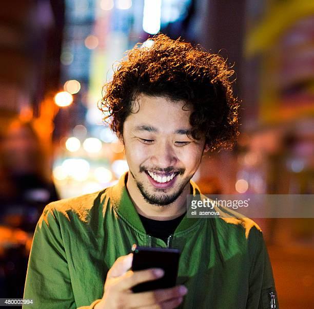 Japonais heureux jeune homme avec le téléphone intelligent de nuit, Tokyo.