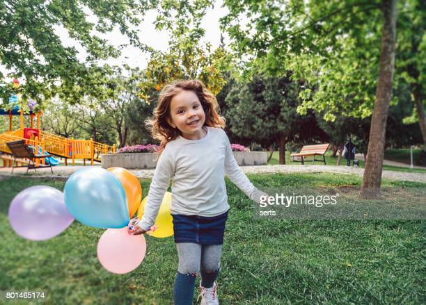 Happy kid girl playing with colorful bunch of balloons