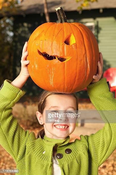 幸せな子供秋のハロウィーンカボチャを手で彼女の頭