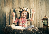 Happy kid playing in pilot helmet near the wooden background