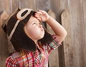 Happy kid playingin pilot helmet near the wooden background