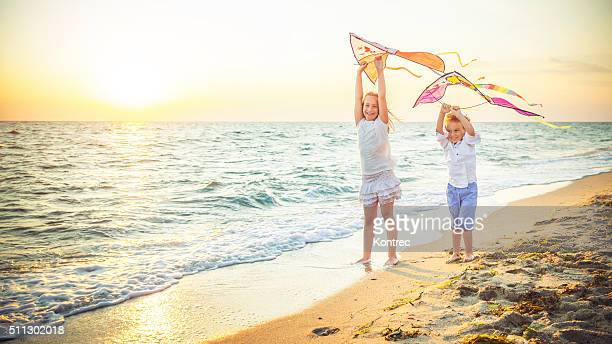 Happy kids flying kites at the beach