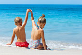Happy kids have fun in sea surf on white sand beach. Couple of children sit in water pool with hands up. Travel lifestyle, swimming activities in family summer camp. Vacations on tropical island.