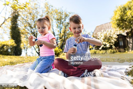 Happy kids having fun with bubble wand in nature.