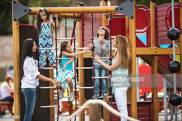 Happy kids having fun with their mothers at the playground.