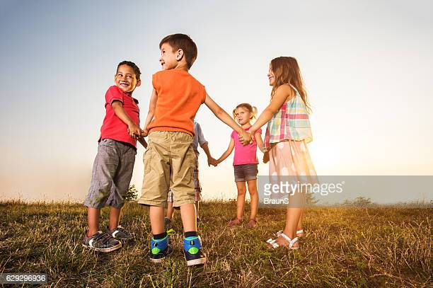 Happy kids holding hands in a circle at sunset.