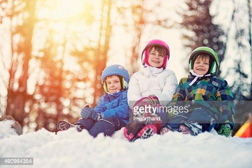 Happy kids in ski outfits enjoying winter