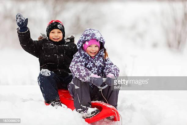 Glückliche Kinder mit Schlitten