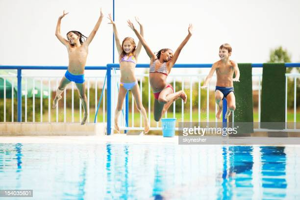 Happy kids playing and having fun together in the pool.