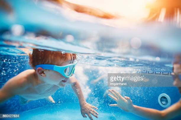 Happy kids playing tag underwater