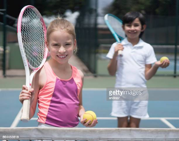 Happy kids playing tennis outdoors