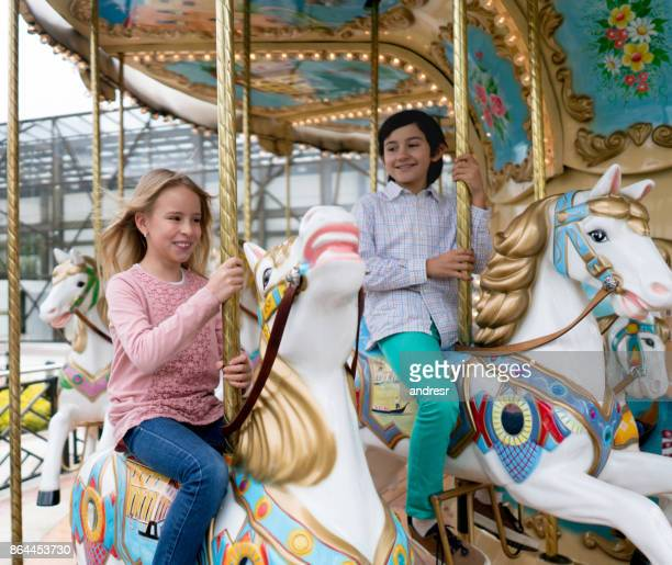 Happy kids riding on the carrousel at the fun fair