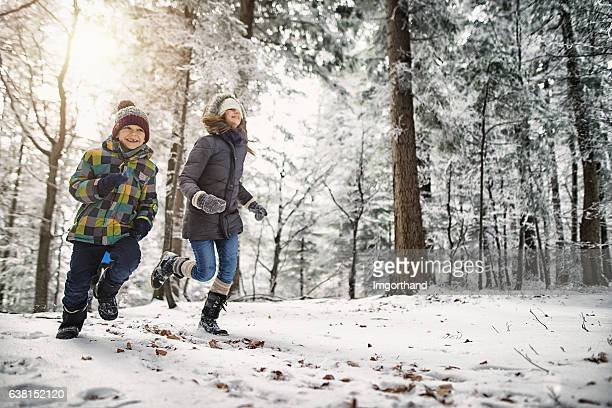 Happy kids running in beautiful winter forest or park