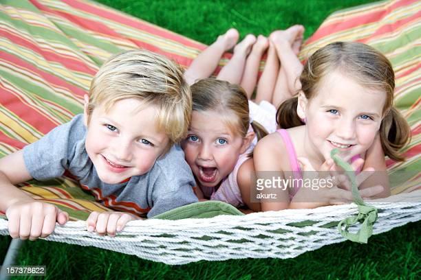 Glückliche Kinder in einer Hängematte Schwingen