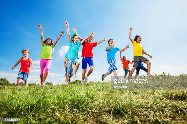 Happy kids with raised arms running against the sky.