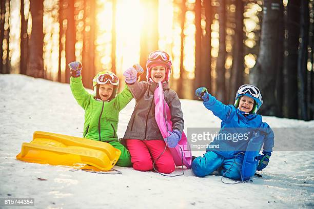 Happy kids with toboggans enjoying winter