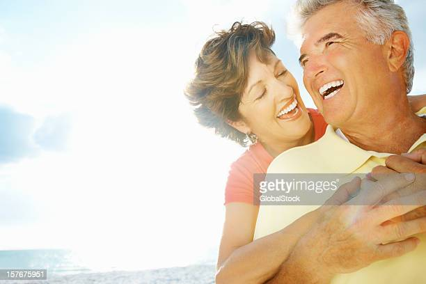Happy lady embracing mature man from behind on a beach