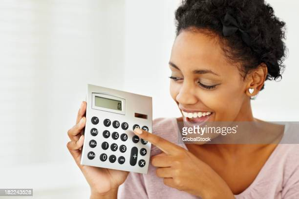 A happy lady holding a calculator in her right hand