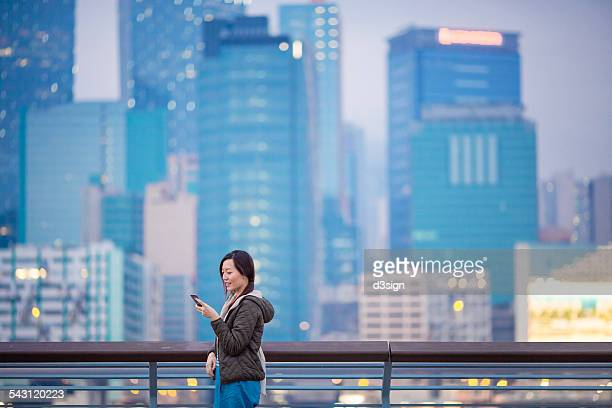 Happy lady leaning on fence while using smartphone