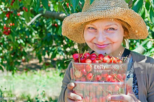 Happy lady with cherries under a cherry tree