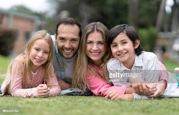 Happy Latin American family lying on the floor outdoors