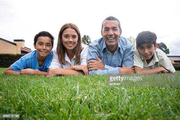Happy Latin American family lying outdoors