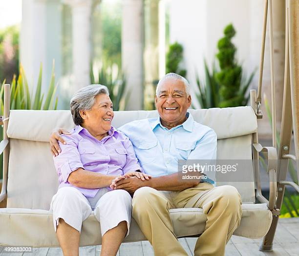 Happy latin couple sitting on swing