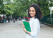 Happy latin female student with curly hair and white shirt outdoor in the city