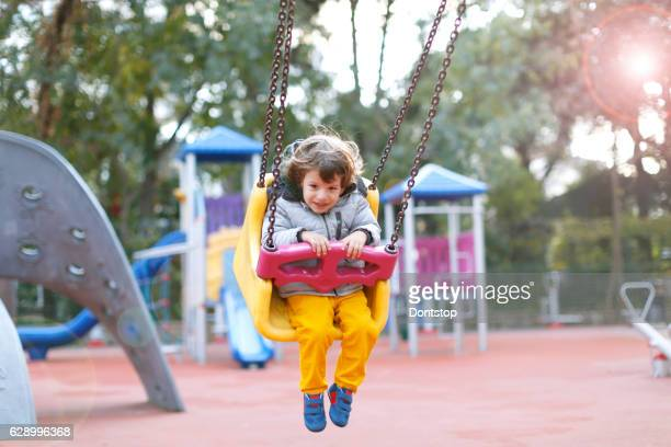 Happy laughing baby boy in swing on playground